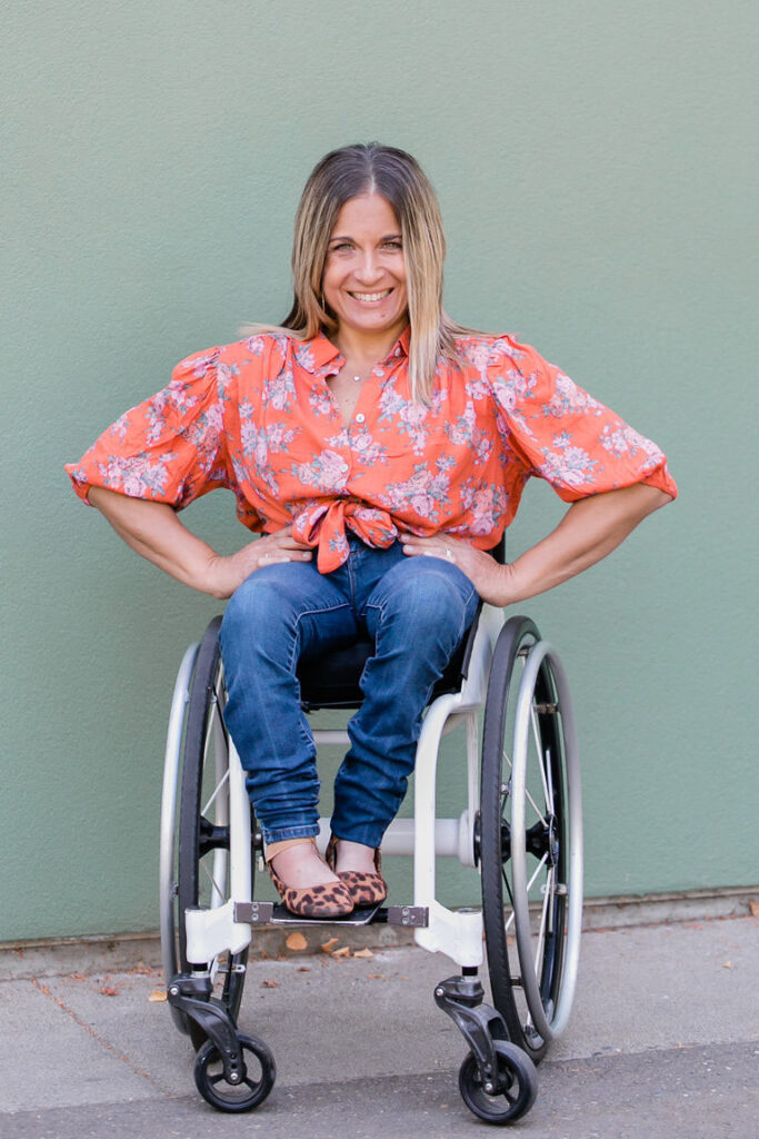 Picture of Alycia smiling hands on hip and elbows out in her wheelchair in front of a pale green wall.