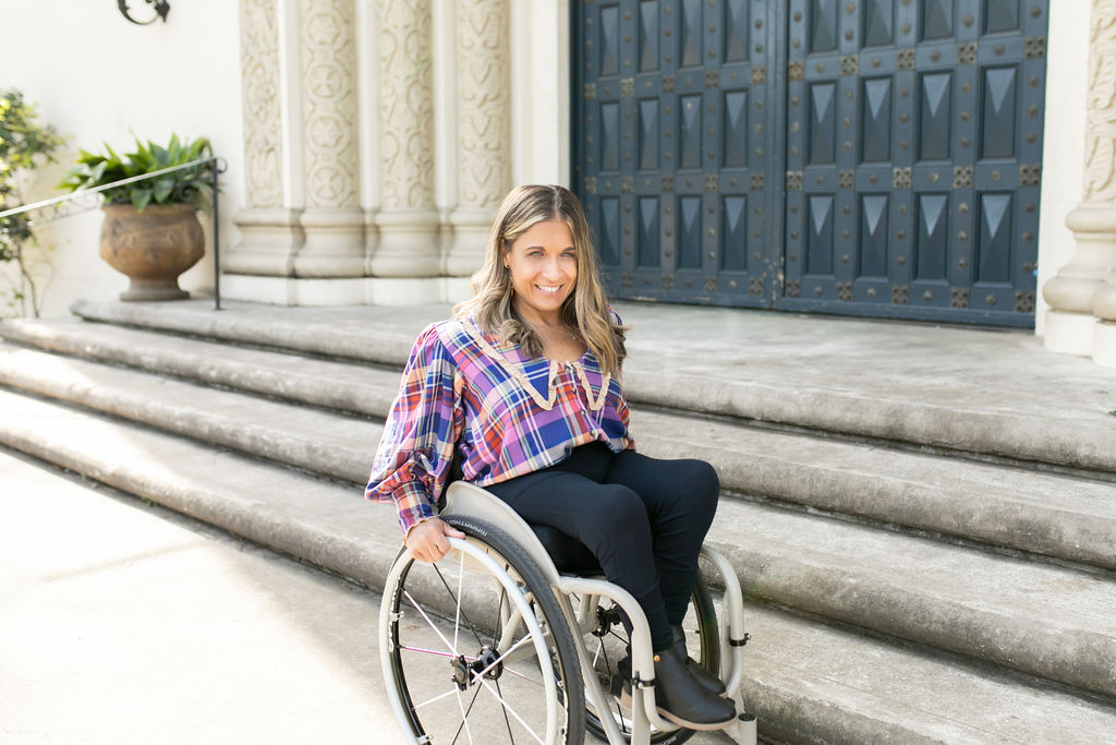 Alycia in her wheelchair in front of a door that has stairs to get up to the door