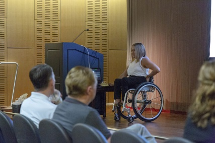 alycia delivering a speech on a stage in her wheelchair sitting next to a podium